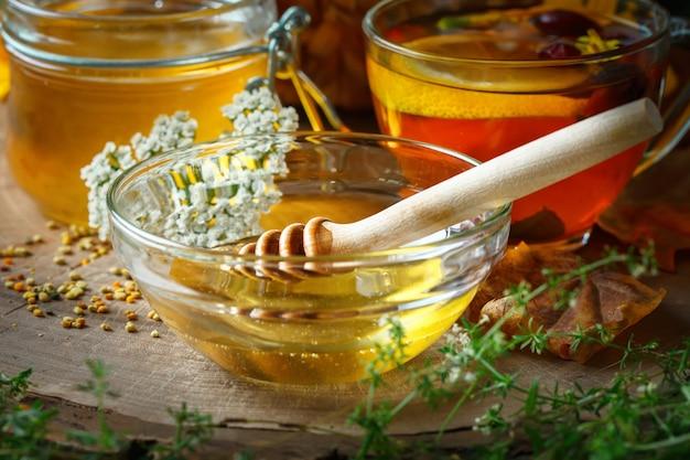 Delicioso mel fresco e uma xícara de chá saudável com limão e roseira na mesa de madeira. foco seletivo.