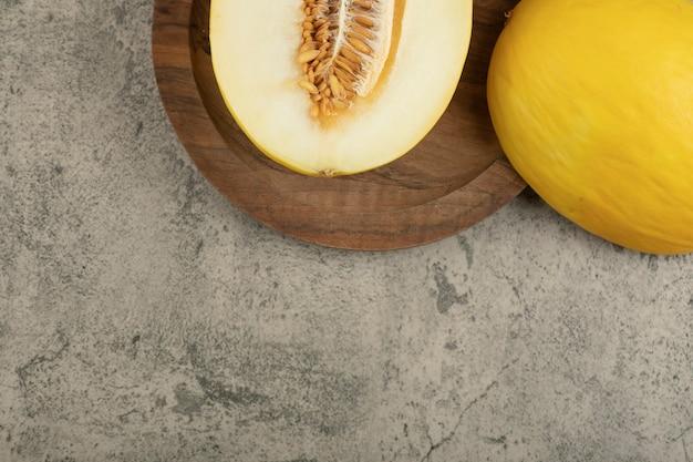Delicioso melão amarelo cortado ao meio e inteiro na placa de madeira.