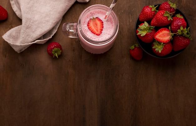 Delicioso milkshake de morango com canudo e copie espaço