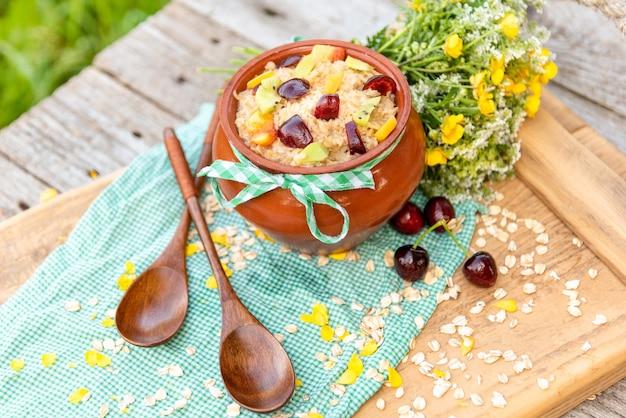Delicioso mingau de aveia com frutas vermelhas no café da manhã em uma panela de barro.