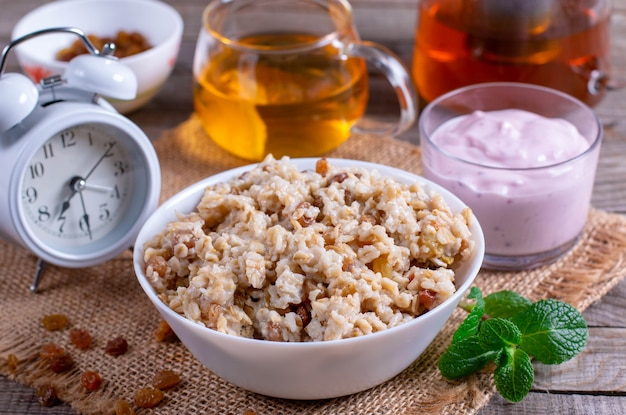 Delicioso mingau de aveia com passas, manteiga e mel em um prato branco sobre um fundo de madeira. café da manhã
