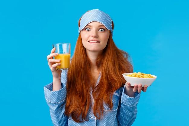 Delicioso. mulher comendo comida favorita de manhã. mulher de faculdade ruiva bonita em máscara de dormir e roupa de dormir, lambendo os lábios da tentação e satisfação, comendo cereais saborosos e suco de laranja
