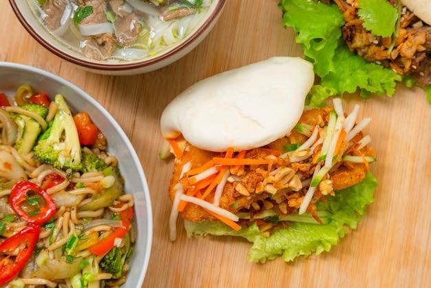 Delicioso pão bao cozido no vapor na mesa de madeira com frango frito e legumes frescos - salada, cenoura e amendoim torrado. comida de rua popular