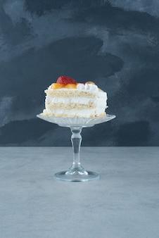Delicioso pedaço de bolo em prato de vidro com fundo de mármore