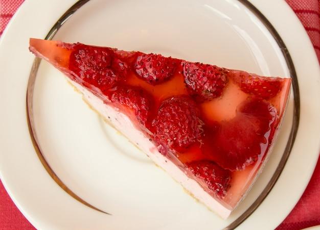 Delicioso pedaço de cheesecake de morango em um prato branco, na mesa com um guardanapo xadrez vermelho, vista superior.