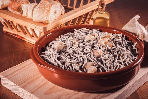 Delicioso prato de enguias com camarão e pão sobre uma mesa de madeira