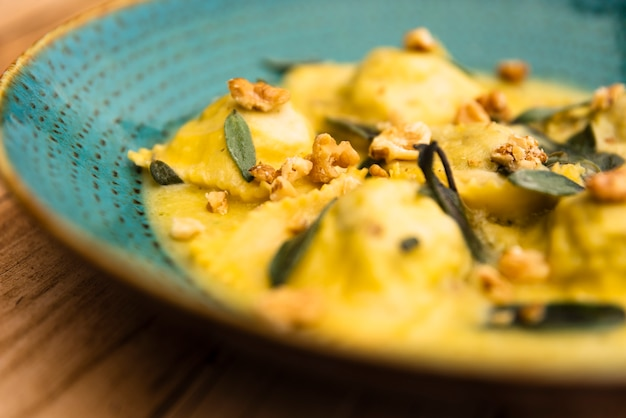 Delicioso prato de massa de ravioli cozido na mesa de madeira
