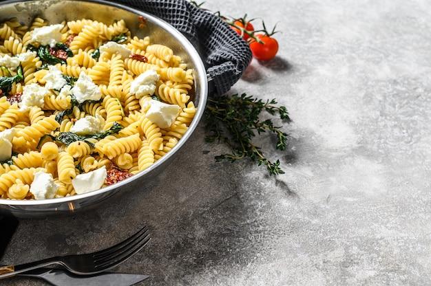 Delicioso prato de massa fusilli com molho cremoso de espinafre e tomates secos. plano de fundo cinza. vista do topo.