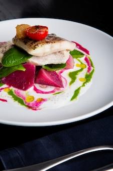 Delicioso prato de restaurante de peixe branco, lúcio, robalo com legumes sob o molho no restaurante