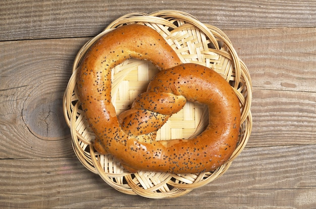 Delicioso pretzel com sementes de papoula em prato de vime na mesa de madeira, vista superior