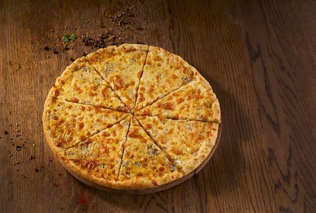 Delicioso quadmagro formaggi, pizza de quatro queijos, vista superior na mesa de madeira