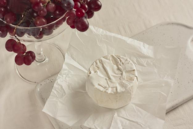 Delicioso queijo brie ou camembert na mesa com cacho de uvas. lacticínios. queijo italiano, francês. foco seletivo