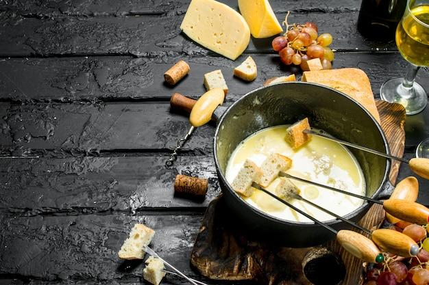 Delicioso queijo fondue com vinho branco na mesa rústica preta.