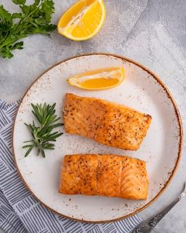 Delicioso salmão cozido com limão em um prato vista superior close