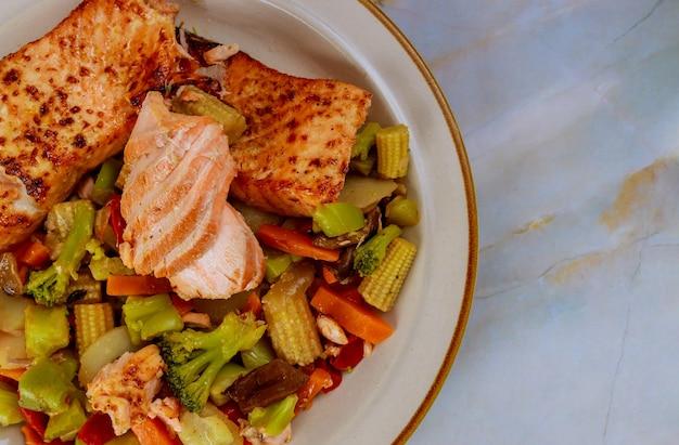 Delicioso salmão grelhado com legumes salteados asiáticos no prato. copie o espaço.
