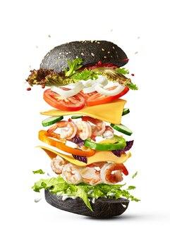 Delicioso sanduíche caseiro de camarão de ingredientes voadores, vegetais orgânicos frescos e pão preto sobre um fundo branco com espaço de cópia.