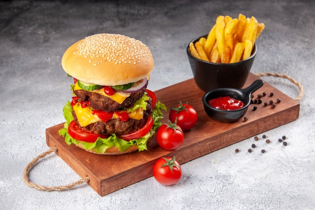 Delicioso sanduíche caseiro de tomate com molho de pimenta batata frita na tábua de madeira na superfície desfocada