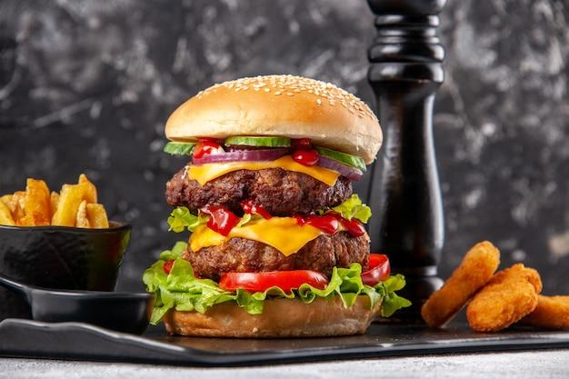 Delicioso sanduíche caseiro e batatas fritas com ketchup nuggets de frango no quadro negro sobre superfície cinza