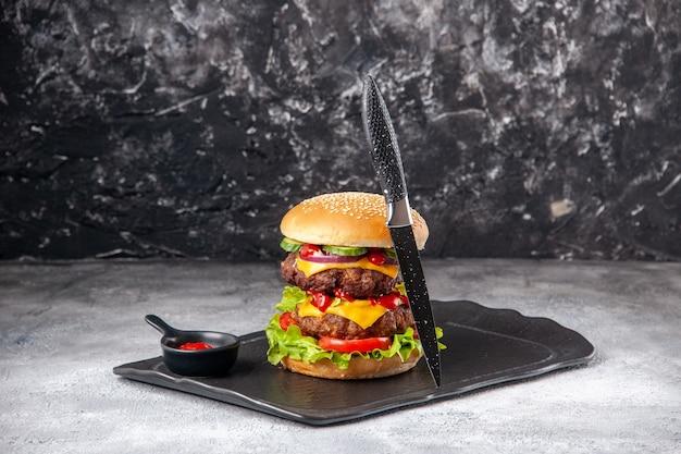 Delicioso sanduíche caseiro e garfo na bandeja preta na superfície cinza angustiada isolada