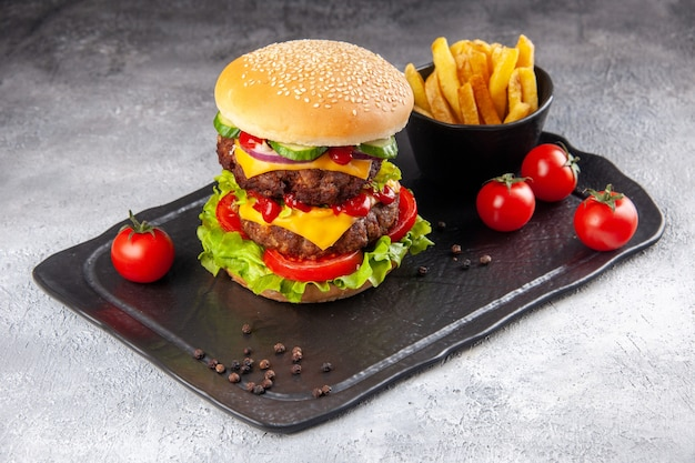 Delicioso sanduíche caseiro e ketchup de batata frita no quadro negro sobre superfície cinza de gelo