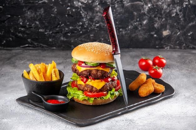 Delicioso sanduíche caseiro e nuggets de frango fritas com ketchup em tomate com caule em superfície cinza de gelo