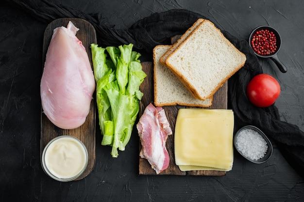 Delicioso sanduíche com ingredientes de pão torrado, em fundo preto, vista de cima