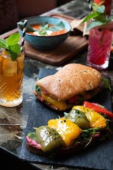 Delicioso sanduíche com molho, verduras, pimentões assados e copos de suco fresco com canudos