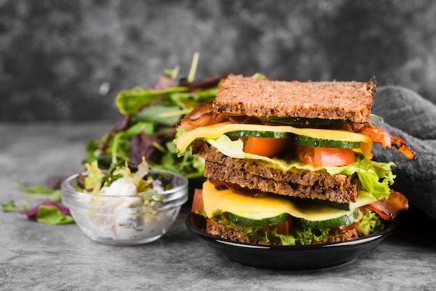 Delicioso sanduíche com salada ao lado
