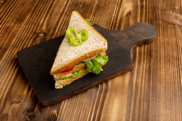 Delicioso sanduíche com tomate salada verde e presunto no marrom