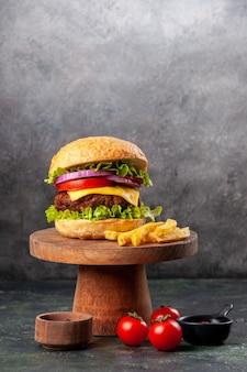 Delicioso sanduíche de batata frita em uma tábua de madeira, tomate e pimenta na superfície da mistura escura