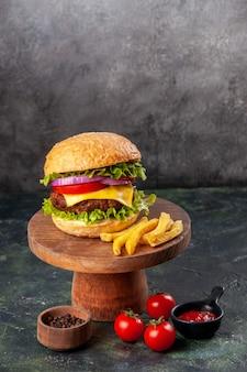 Delicioso sanduíche de batata frita em uma tábua de madeira, tomate, pimenta e pimenta na superfície da mistura escura