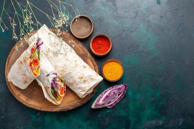 Delicioso sanduíche de carne feito de carne grelhada em um espeto fatiado com temperos na mesa azul escuro.