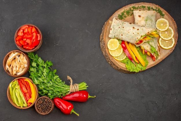 Delicioso sanduíche de carne shaurma fatiado com limão e verduras no fundo escuro sanduíche de hambúrguer com pão maduro.