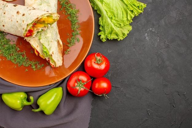 Delicioso sanduíche de shaurma fatiado com legumes frescos no espaço escuro de vista de cima