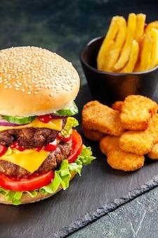 Delicioso sanduíche e nuggets de frango fritas em bandeja de cor escura sobre superfície preta