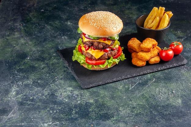 Delicioso sanduíche na bandeja de cor escura e nuggets de frango, tomates e batatas fritas no lado esquerdo na superfície preta