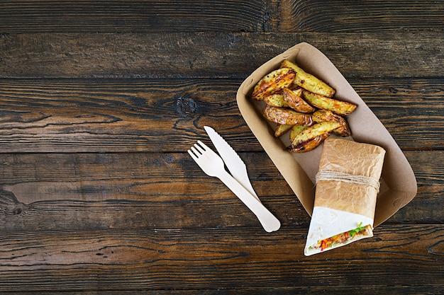 Delicioso sanduíche shawarma com frango e batata na madeira