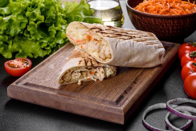 Delicioso shawarma fresco com carne e legumes em uma mesa de concreto escura. fast food, cozinha turca