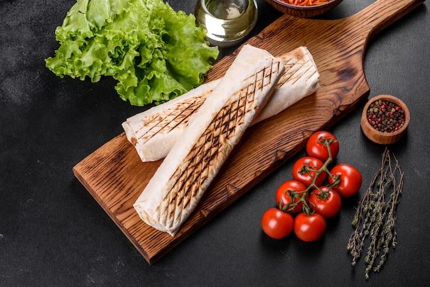 Delicioso shawarma fresco com carne e legumes em uma mesa de concreto escura. fast food, cozinha turca Foto Premium