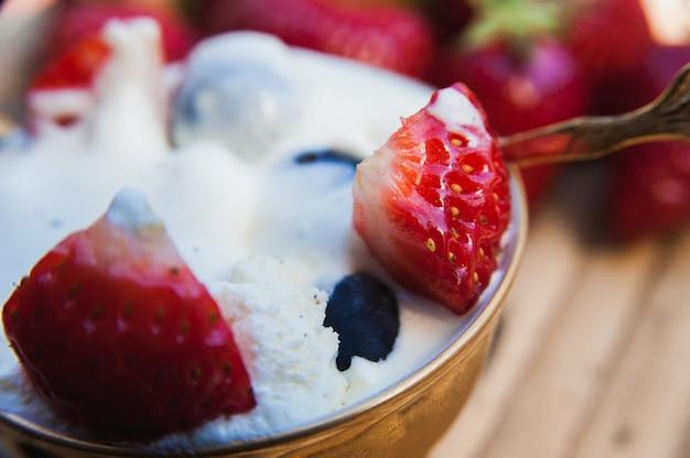 Delicioso sorvete com pedaços de morango e mirtilos
