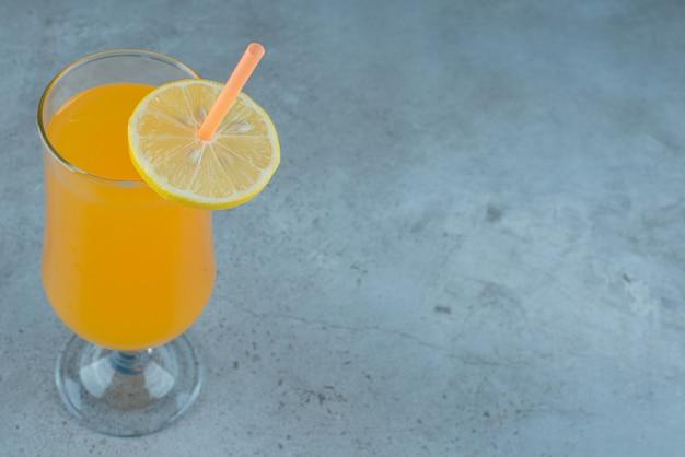 Delicioso suco de laranja com rodela de limão e palha.