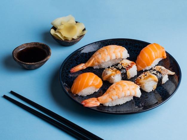 Delicioso sushi apetitoso servido em prato de barro com molho de soja e pauzinhos na horizontal