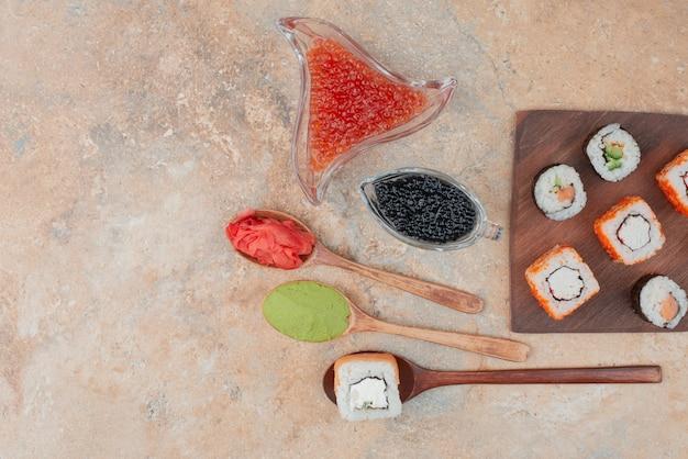 Delicioso sushi com caviar, gengibre e vasabi em prato de madeira