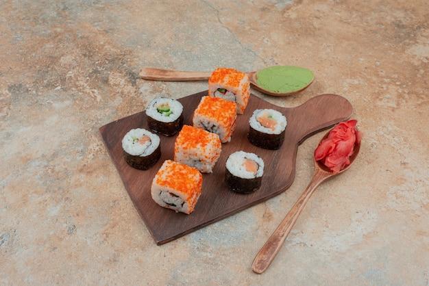Delicioso sushi com caviar, gengibre e vasabi na placa de madeira.