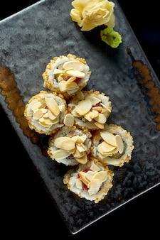 Delicioso sushi crocante com atum, amendoim, pipoca e pepino, servido num prato de cerâmica com gengibre e wasabi.