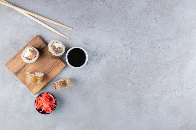 Delicioso sushi fresco rola com molho de soja na placa de madeira.
