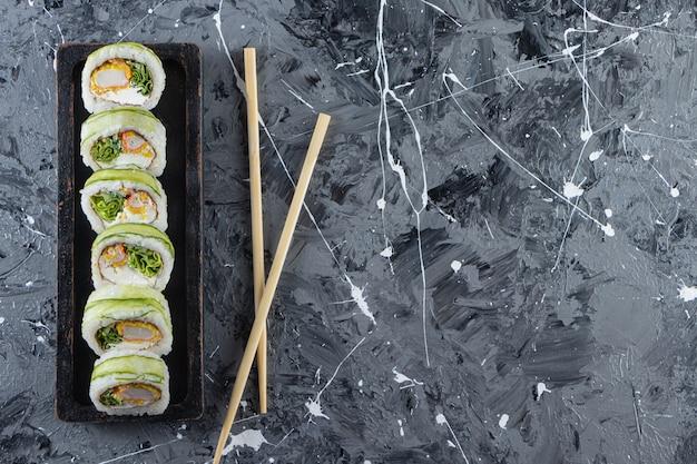 Delicioso sushi rola com atum na mesa de pedra.