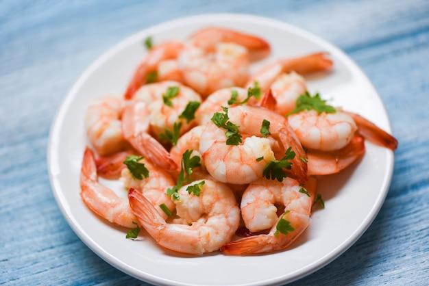 Delicioso tempero de camarão na chapa branca e fundo de mesa de madeira cozido de camarão ou camarão, frutos do mar egoísta