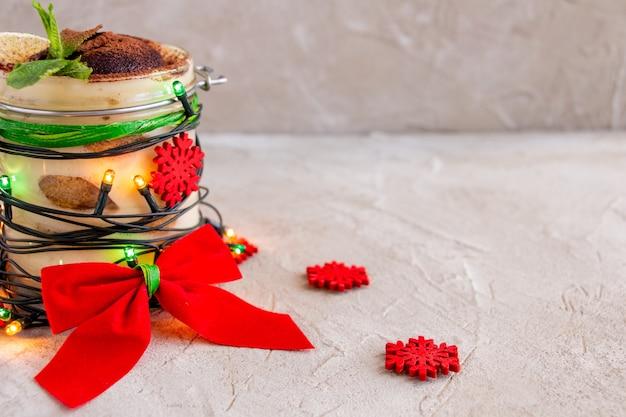 Delicioso tiramisu decorado com luzes de natal, flocos de neve com arco vermelho, natal ano novo
