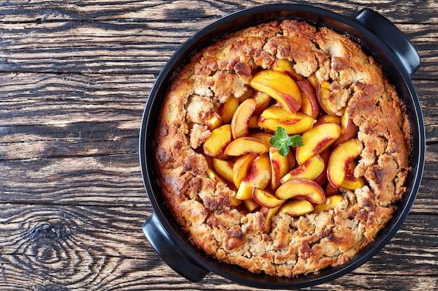 Delicioso torta de pêssego com uma crosta de massa doce, o melhor para um café da manhã saudável, vista horizontal de cima, camada plana, close-up